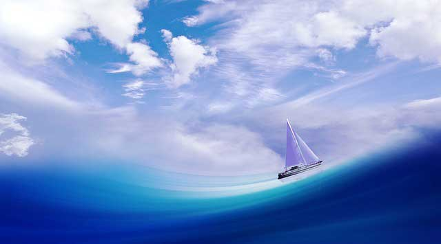 Sailboat navigating waves on a clear day
