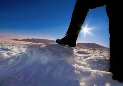 Man trekking in snow, sunny winter day
