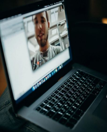 Picture of a laptop with someone videoconferencing